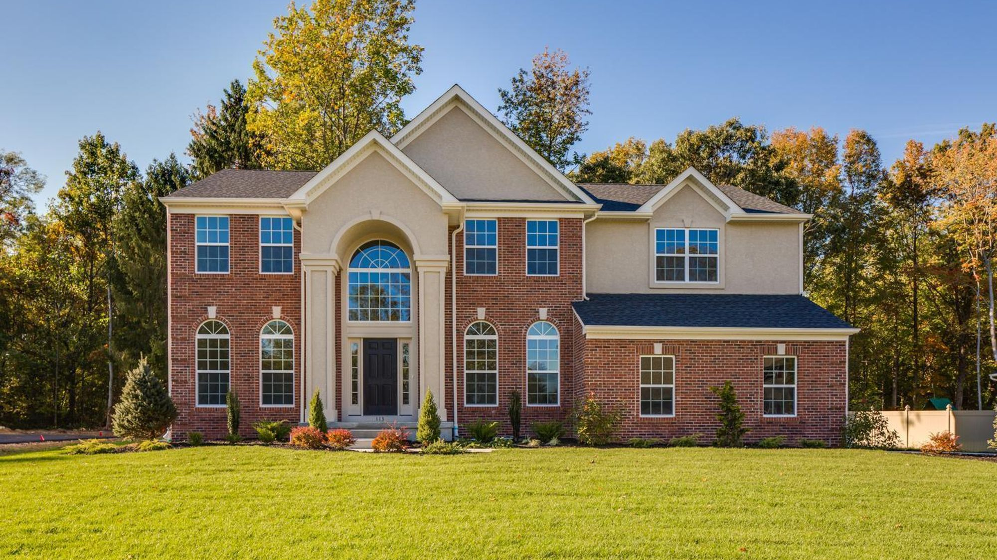 Exterior of the Baldwin Traditional model luxury new home in south NJ with brick front and soaring 2 story columns and transom windows.