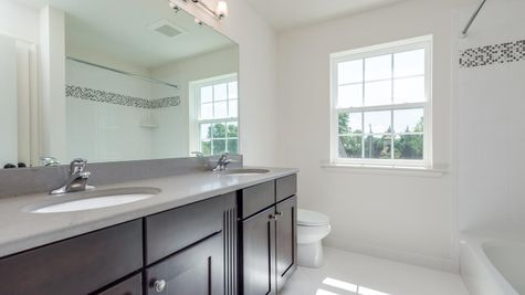 Badwin hall bath with shower over tub and double sink vanity.