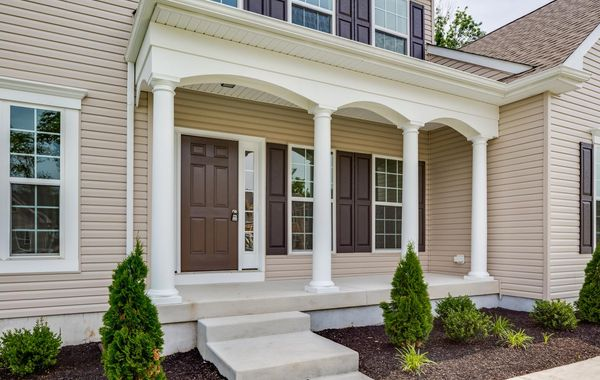 The Augusta Traditional new home in NJ with cream siding, dark shutters, small front porch with columns, 2 stories.