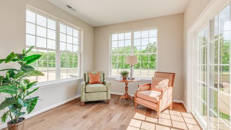 Primrose model new home sun room with wood floor, many windows and sliding glass door to back yard, sample furniture..