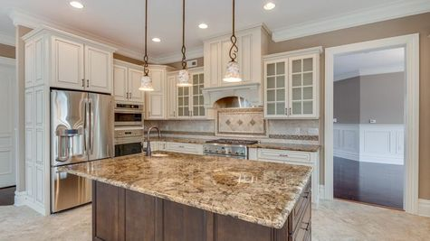 Stoneleigh Kitchen center island, pendant lights over island, tile floor, granite counters, light color cabinets - some glass.