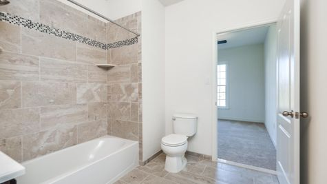Bathroom with shower over tub, plus toilet in view in Avignon model home.
