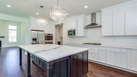 Brandywine model new home in NJ kitchen with white cabinets, two chandeliers & large center island.