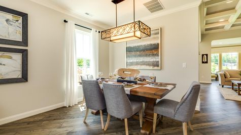 The Jasmine model home Great Room dining area with table, large window, chandelier, wood floors, more living areas in backgroun.