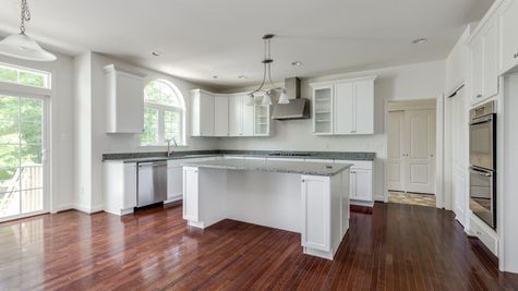 Baldwin model new home in South Jersey, kitchen with white cabinets, double wall oven, island, wood floor.