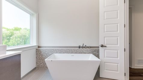 The Stoneleigh Master Bathroom with modern, white, simple, rectangular soaking tub and window above.