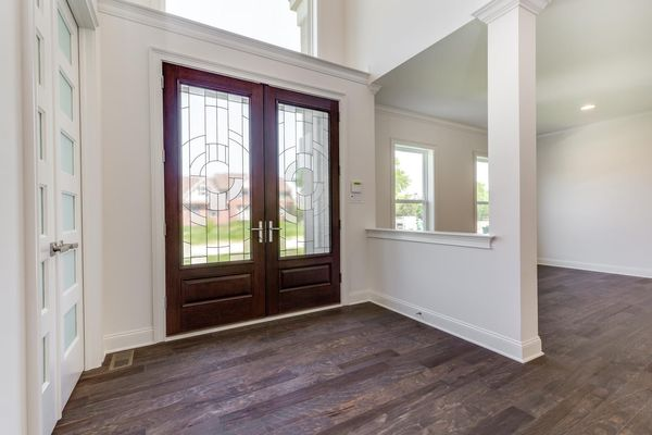 Entry Hall of The Stoneleigh luxury new home model in South New Jersey, featuring double front door with glass inserts, wood floor.