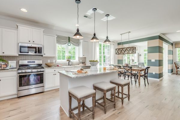 Kitchen in Zinnia model one story new home in south NJ with white cabinets, three pendant lights over center island, eating area.