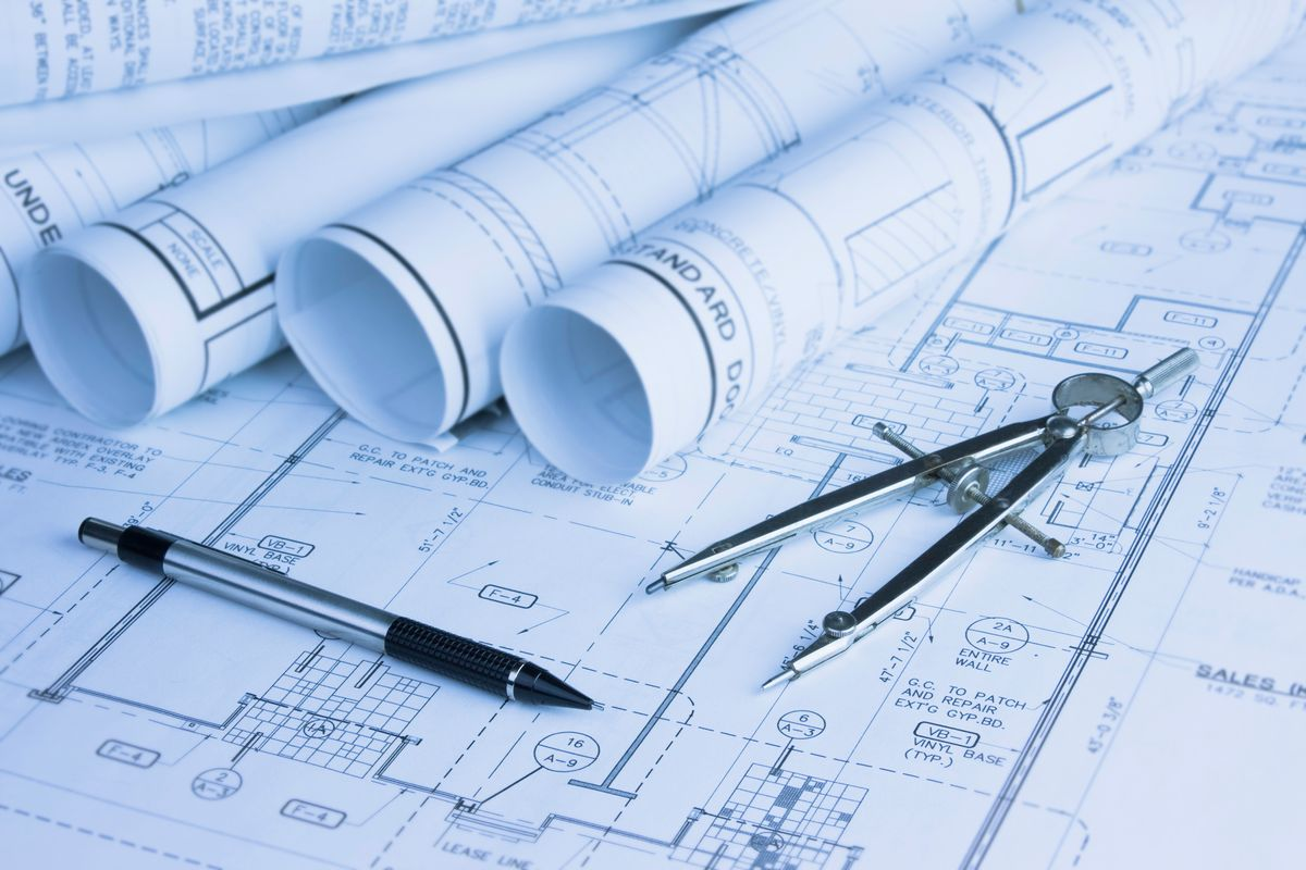 Rolled blueprints showing new home designs for construction on your lot