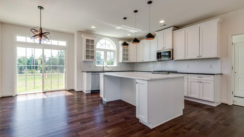 Baldwin model kitchen with white cabinets, granite counters, large island, eating area and slider doors to outside.