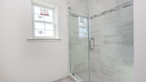 Walk-in shower with glass doors and pale gray tiles in Avignon single story model new home in NJ.