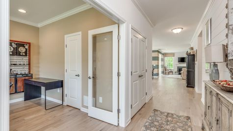 View into interior of the Zinnia one story model new home from front entrance, with room on left, living areas ahead.