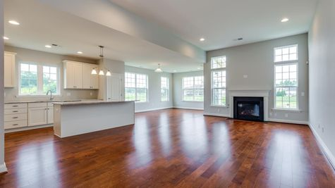 Open living area in Magnolia with fireplace, many windows, wood floors, white walls, kitchen off to the left side.