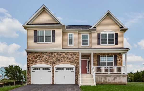 Oakton Grand new home in NJ with tan siding & stone facade, dark shutters, double peak roofline, veranda, 2 garages.