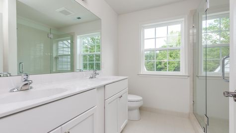 Baldwin hall bathroom with double sinks and walk-in shower with glass doors.