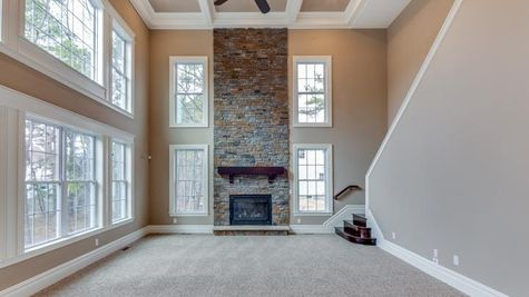Two story Stoneleigh family room with stone fireplace, many two story high windows, back staircase to second floor.