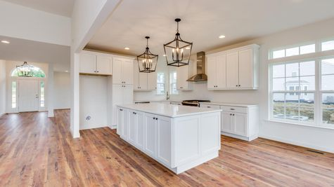 Avignon model new home in NJ, one story, view of kitchen with white cabinets, wood floors.