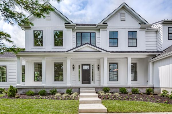Large luxurious quick delivery new home in Moorestown NJ with white siding, black front door, front porch, black framed windows.