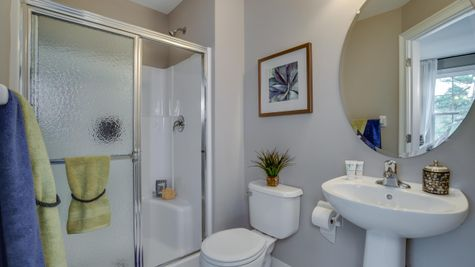 Bathroom attached to a bedroom in Brandywine with shower over tub and pedestal sink.