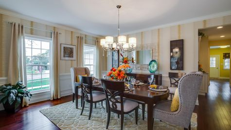 Formal dining room in Brandywine model home with wood floors, two large windows, chandelier and sample furniture.