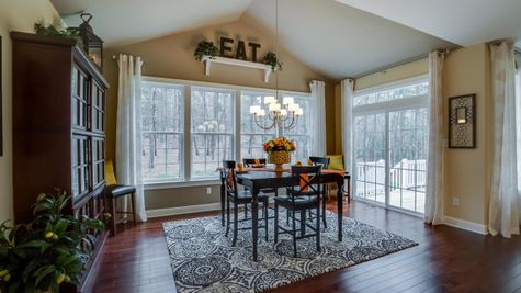 Eating area next to kitchen in Brandywine model new home with sliding doors to outside, wood floors, chandelier.