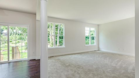 Family Room of the Ashton model home with many windows, white walls, pale carpet.