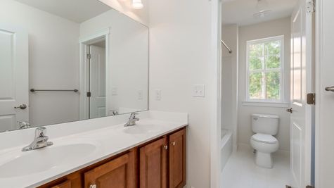 The Ashton Hall bathroom on second floor with double sink and wood cabinets.