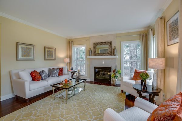 Formal living room with fireplace and large windows, wood floors in Bandywine model new home.