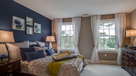 A bedroom in Brandywine model new home with two large windows, carpet and sample furniture.