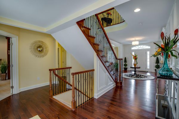 Stairs with decorative handrails in Brandywine model new home plus sample decor visible.
