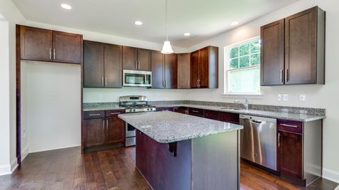 Kitchen of the Ashton model home with dark cabinets, central island and wood floor.
