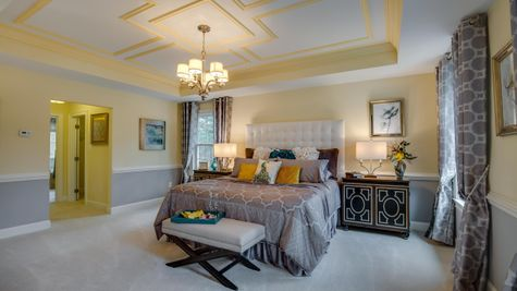 Master bedroom in Brandywine luxury new home, large with carpet, sample furniture.
