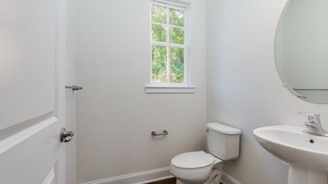 Powder room of the Ashton model home with toilet, sink, mirror, window and white walls.