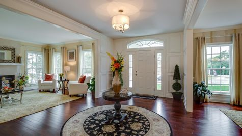 Front hall and door of Brandywine new luxury home in NJ with wood floors, sample decor, living room to left, dining room on right.