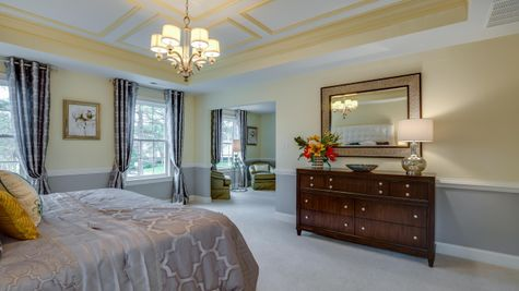 Brandywine model new home large master bedroom with sitting area, carpet, sample furniture.