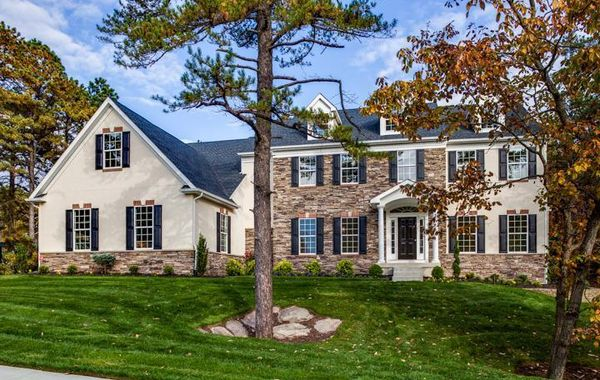 Exterior of Brandywine Manor luxury new home in South NJ with stone and stucco and dark shutters.