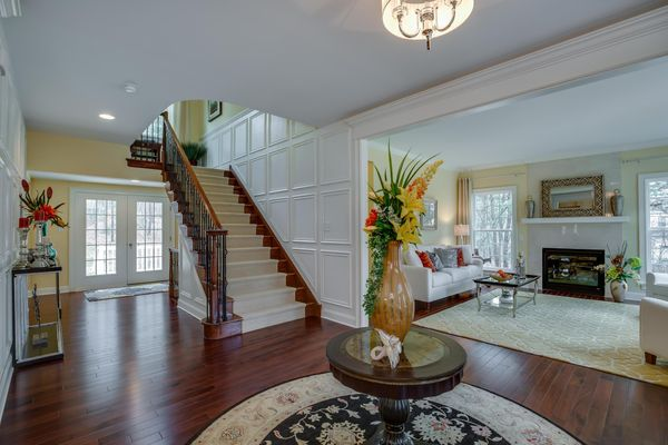 Front hall of Brandywine luxury model home with flower arrangements, stairs in view and formal living room to right.