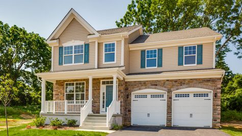 The Ashton Grand model new home in South Jersey , 2 stories with tan siding and stone front, green shutters, plus porch.