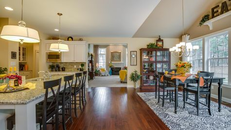 Brandywine model luxury new home in NJ kitchen & eating area with wood floors, center island, sample furniture.