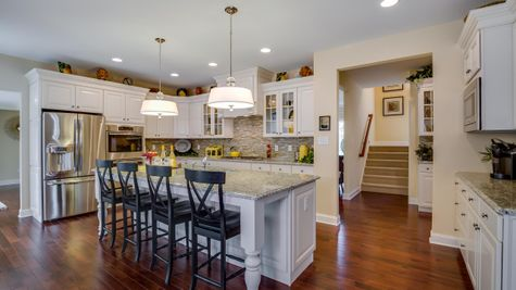 Brandywine kitchen with white cabinets, wood floors, large center island with four bar height chairs.