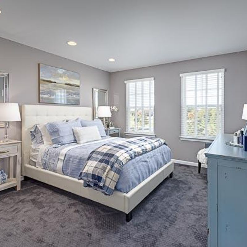 A bedroom with grey carpet