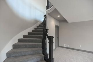 Curved Staircase with Upgraded Stair Carpet leads to the Walk Out Finished Lower Level that has 2 Bedrooms, Living Room and a Wet Bar that Walks out to the Covered Deck on a Wooded Private Lot. Picture is of Actual Home.