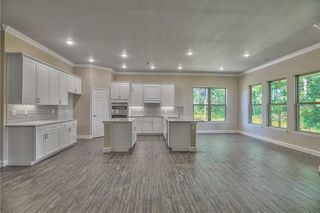 View of Kitchen, Dining Room and Great Room with Corner Stone Front Gas Fireplace. Tile Floors that look like Wood Planks. Corner Pantry, Granite Counter Tops, Under Cabinet Lighting, Upgraded Tile Backsplash and Stainless Steel Appliances. Picture is of Actual Home.