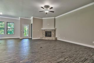 View of Great Room with  Corner Stone Front Gas Fireplace. Tile Floors that look like Wood Planks. Picture is of Actual Home.