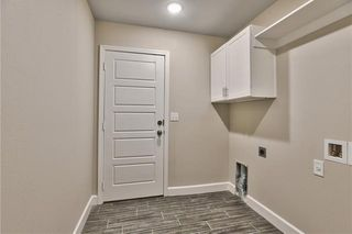 Laundry Room conveniently located  right off the Interior Garage Door. Upper Cabinet with Hanging Space. Picture is of Actual Home.