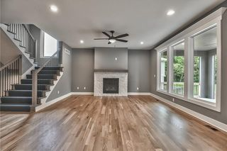 Great Room with Hardwood Floors and Stone Front Gas Fireplace with Mantel