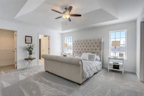 Gray master suite in a new home by Tim O'Brien