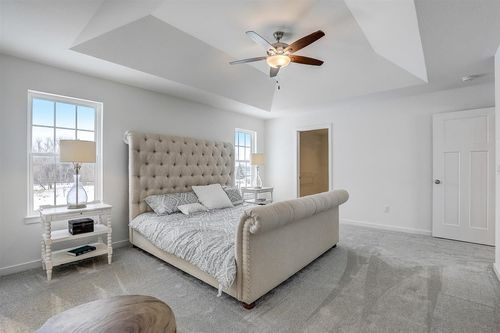 Owner suite with a tray ceiling in a home in Milwuakee, WI