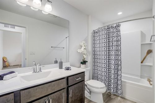 Gray bathroom in a new home by Tim O'Brien