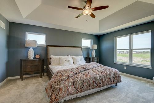 Master suite with a tray ceiling in a new home by Tim O'Brien